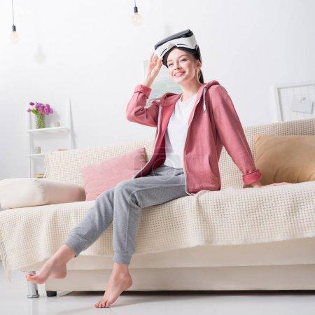 Photo pour Fille souriante tenant casque de réalité virtuelle et regardant loin à la maison - image libre de droit