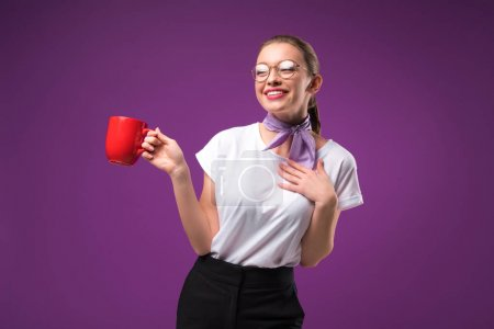 smiling girl posing with red cup of coffee isolated on purple