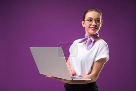 smiling girl holding laptop and looking away isolated on purple