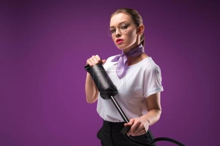 girl holding pump and looking at camera isolated on purple