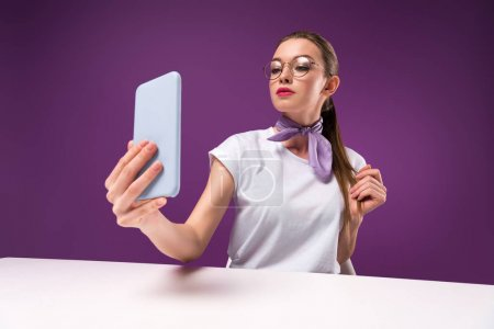 Photo for Girl taking selfie with smartphone isolated on purple - Royalty Free Image