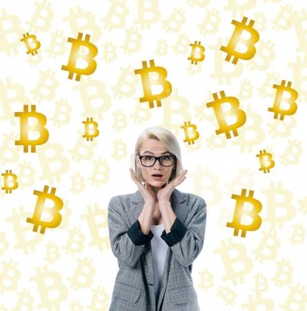 beautiful shocked businesswoman posing in formal wear and bitcoin symbols on white