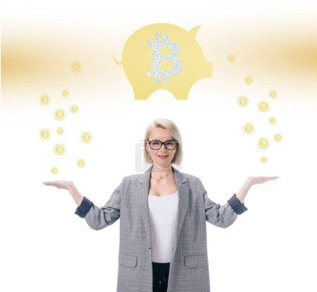 séduisante femme d'affaires élégante avec Bitcoin et les symboles de tirelire sur blanc