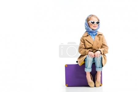 View of stylish kid in headscarf and sunglasses sitting on suitcase isolated on white