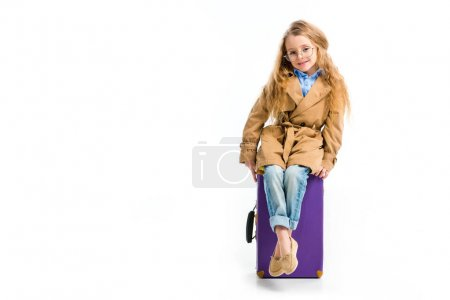 Stylish child in glasses and trench coat sitting on suitcase isolated on white