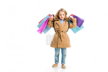 Photo for Kid in trench coat standing with different shopping bags in hands isolated on white - Royalty Free Image