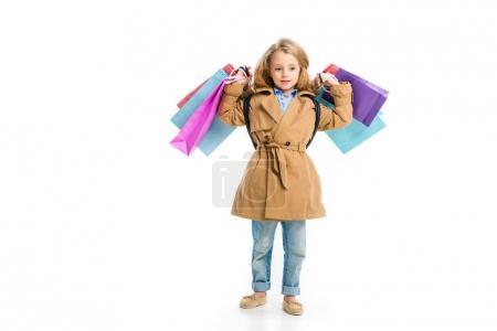 Photo pour Kid en Trench-Coat debout avec différents sacs à provisions en mains isolés sur blanc - image libre de droit
