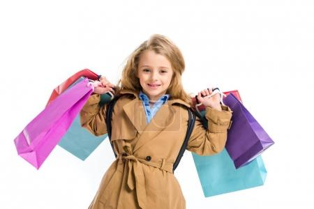 Photo for Smiling child wearing trench coat and holding bunch of shopping bags isolated on white - Royalty Free Image
