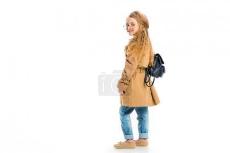 Photo pour Vue arrière de l'enfant souriant dans les verres portant trench-coat et tenant sac isolé sur blanc - image libre de droit