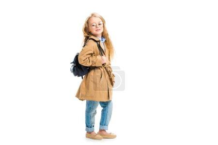Vue latérale du kid en verres tenant sac et porter Trench-Coat beige isolé sur blanc