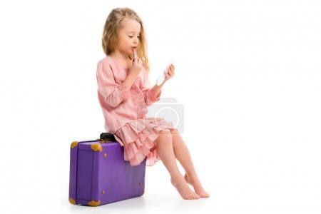 Photo pour Vue latérale de l'enfant élégant assis sur la valise et faisant maquillage par rouge à lèvres isolé sur blanc - image libre de droit