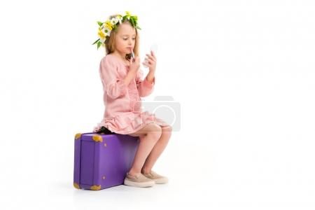 Side view of kid sitting on purple suitcase and doing makeup by lipstick isolated on white