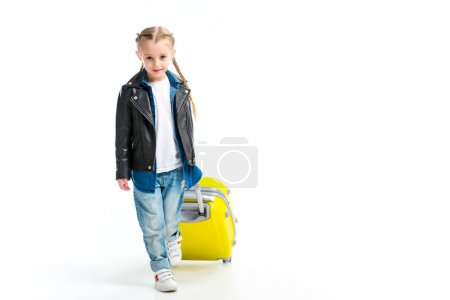 Front view of little child carrying yellow wheel suitcase isolated on white