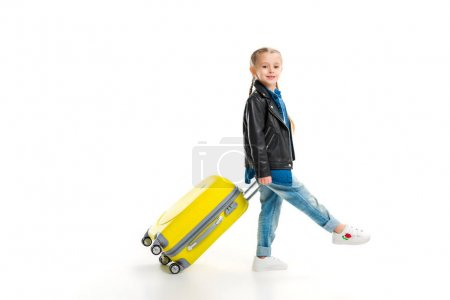 Side view of little tourist with pigtails carriyng her yellow wheel suitcase isolated on white