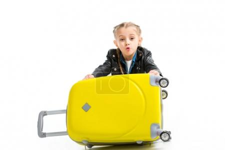 Excited little tourist holding yellow wheel suitcase isolated on white