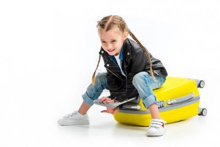 Photo pour Enfant avec des nattes, assis sur la valise de roue couchée isolé sur blanc - image libre de droit