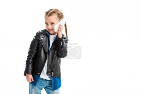 Smiling stylish kid wearing leather jacket and talking on smartphone isolated on white