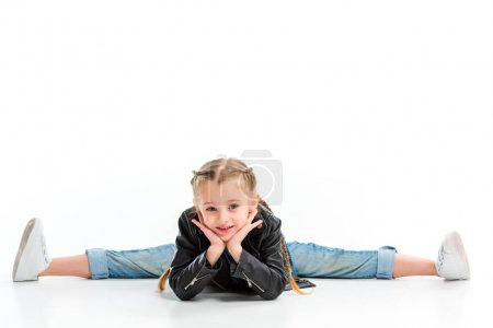 Stylish kid with pigtails sitting on split and holding hands on chin isolated on white