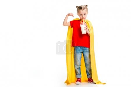 Supergirl in yellow cape drinking milkshake and showing muscles on hand isolated on white