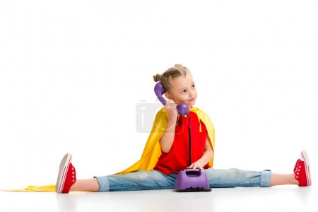 Happy supergirl sitting on split and talking on phone isolated on white