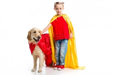 Dog in red cape with supergirl in yellow cape standing beside isolated on white