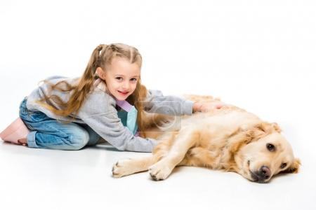Portrait of happy kid touching lying beige dog isolated on white