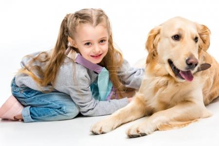 Closeup view of smiling little kid with lying beige dog isolated on white