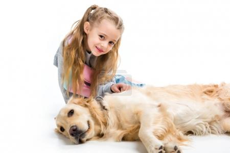 Child and lying dog looking at camera isolated on white