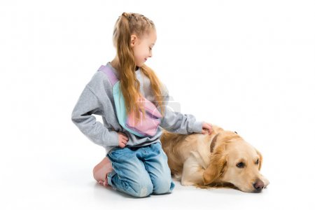 Stylish child stroking lying dog with collar isolated on white