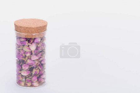 close-up view of dry rose buds in glass jar isolated on white