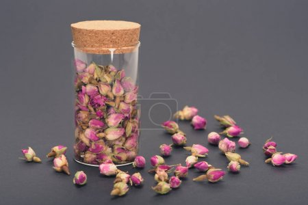 close close-up view of beautiful dry pink rose buds in glass jar on grey