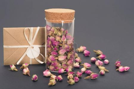 close-up view of dry rose buds in glass jar and envelope on grey