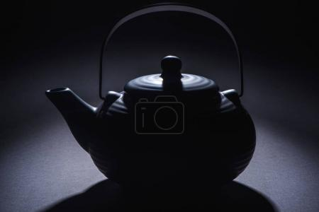 close-up view of black traditional chinese teapot on black
