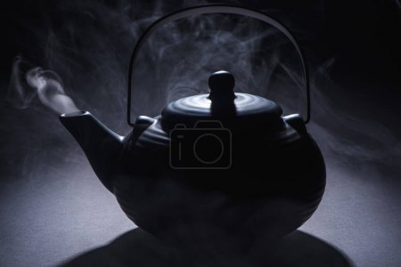close-up view of black chinese teapot with hot steam on black