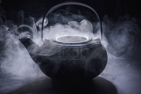 close-up view of black kettle with hot steam on black