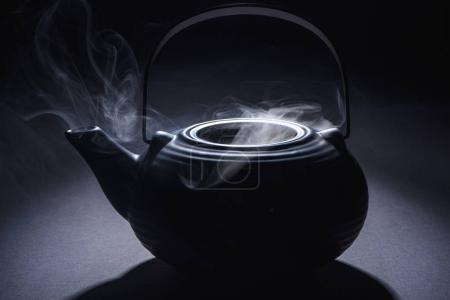 close-up view of black teapot with hot steam on black