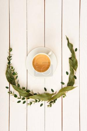 top view of floral wreath and cup of coffee on wooden tabletop