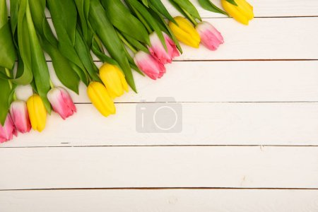 top view of beautiful pink and yellow blooming tulips on wooden surface