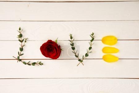 Photo pour Vue de dessus du mot amour fabriqué à partir des éléments floraux sur la surface en bois - image libre de droit