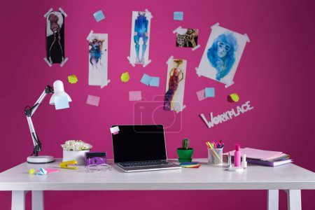 modern designer workplace with fashion sketches and laptop on table