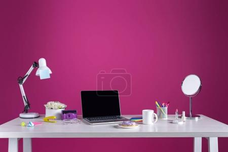 laptop with blank screen, doughnut with coffee, camera, cosmetics and office supplies on pink