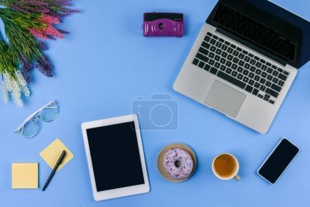 Photo pour Vue de dessus des appareils numériques, fleurs, tasse de café avec beignet et appareil photo sur bleu - image libre de droit