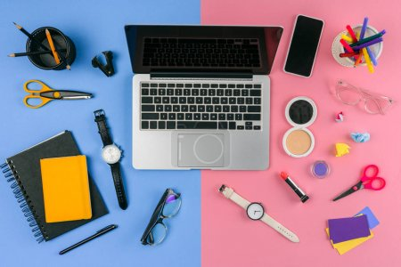 Photo for Top view of laptop, smartphone and cosmetics with office supplies divided at male and female workplace - Royalty Free Image