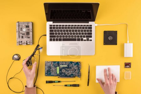partial top view of person holding eyeglasses and fixing laptop on yellow