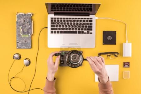 cropped shot of person holding magnifying glass while repairing laptop