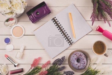 Draufsicht auf leeres offenes Notizbuch mit Stift, Kamera, Blumen, Kosmetik und Tasse Kaffee mit Donut auf Tischplatte