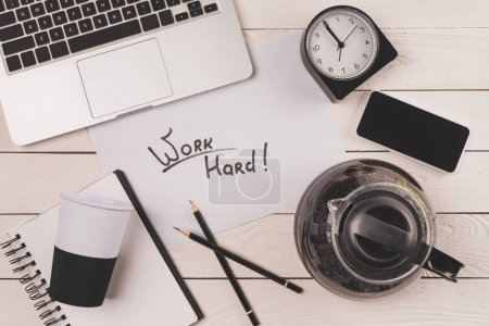 Photo for Laptop, coffee pot, paper cup, clock, smartphone and inscription work hard at workplace - Royalty Free Image