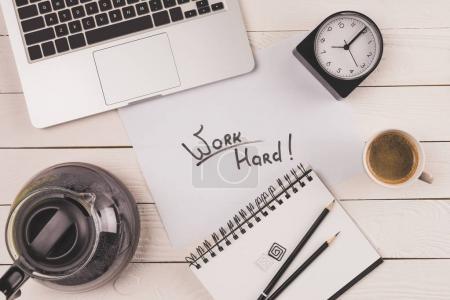 Photo pour Vue du haut de l'ordinateur portable, horloge, café et inscription travailler dur dans le carnet - image libre de droit