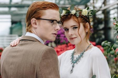 beautiful elegant young red-haired wedding couple standing together in botanical garden