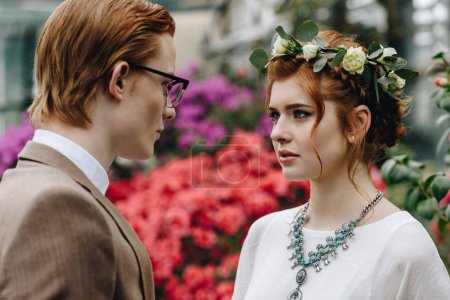 beautiful elegant young red-haired wedding couple looking at each other